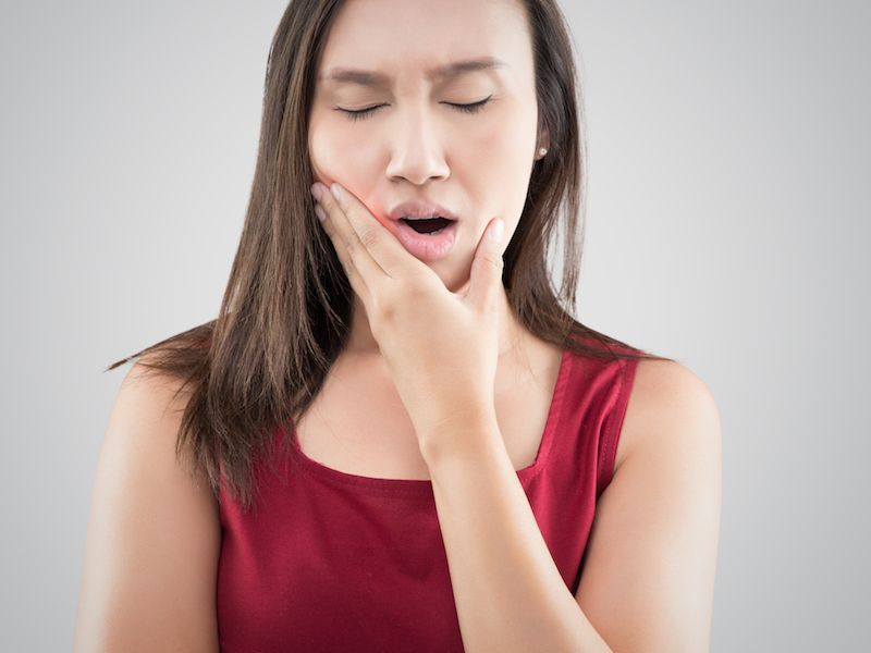Woman with braces holding her swollen gums.