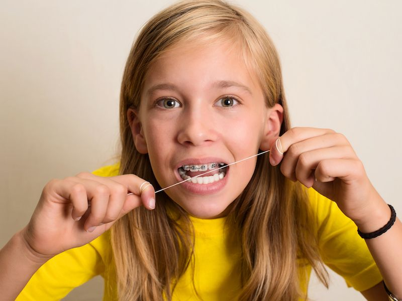 Girl learning to floss her teeth while wearing braces.